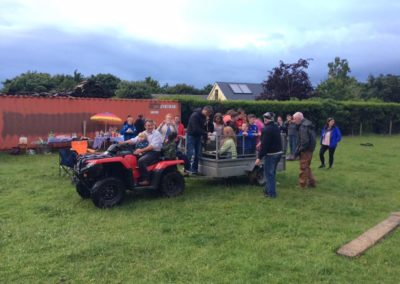 Children in trailer being towed in field Ballintrillick