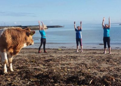 Tralua Trail running team stretching being watched by a cow on Mullaghmore beach