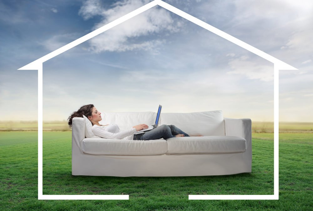 Woman getting news whilst on sofa in field with house around her
