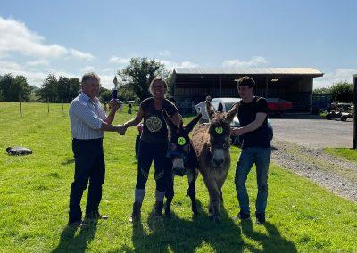 Lisa Lomax receiving donkey derby trophy 2021